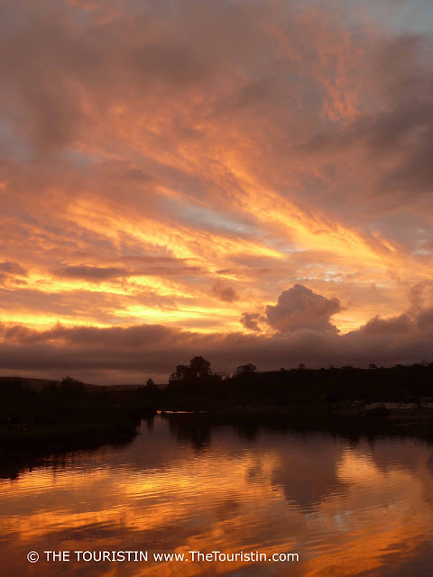 Intense orange- and pastel coloured sunset mirrored in a river.