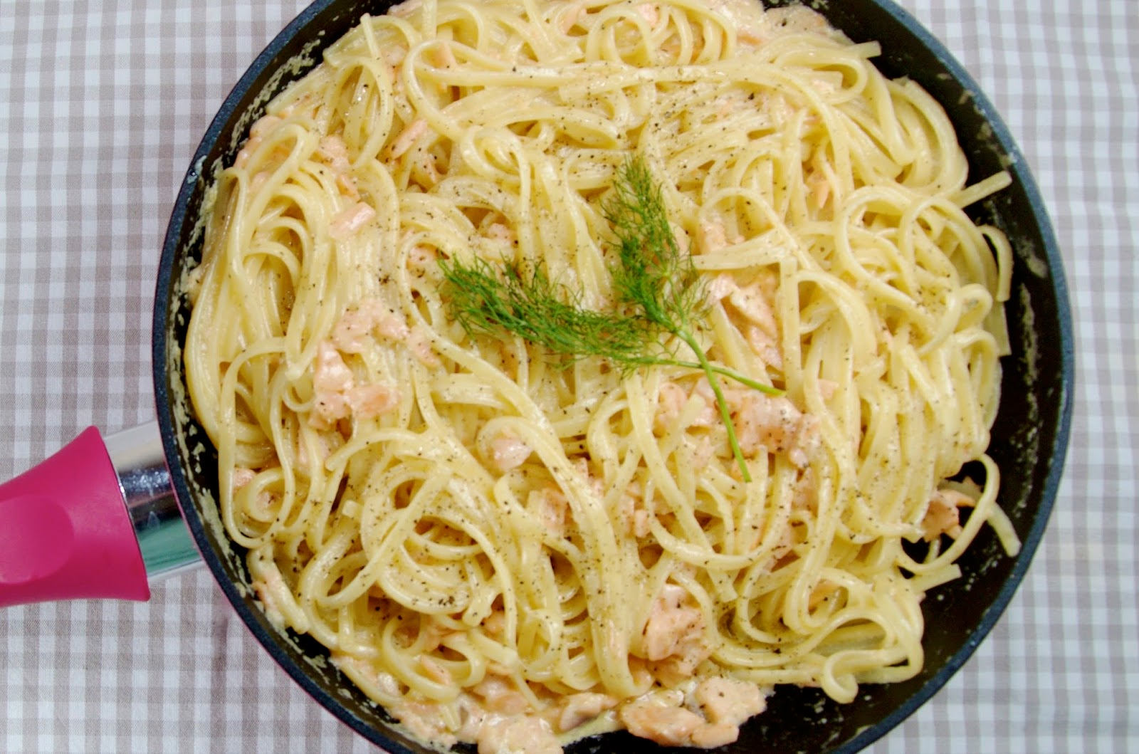 pasta with salmon in pink frying pan