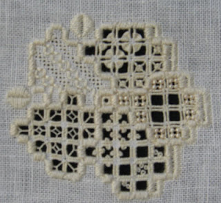 a hardanger embroidered rose made of stitched and cut-away areas