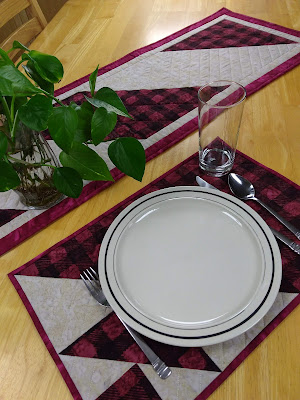 Table setting with red plaid quiltyed placemat