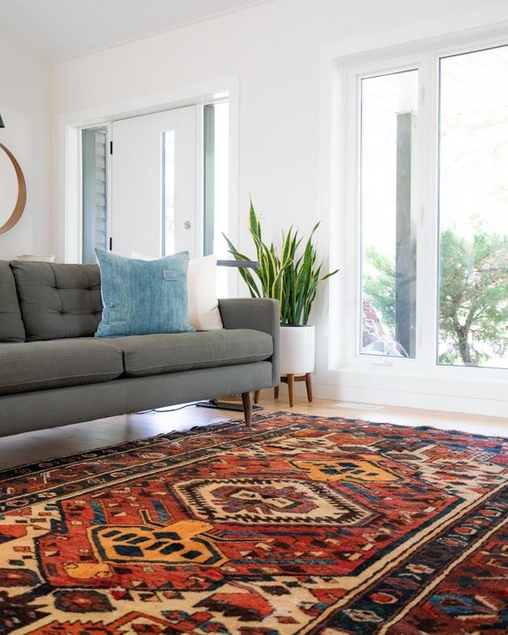 Salón con alfombra étnica y sofá de respaldo bajo en tonos grises