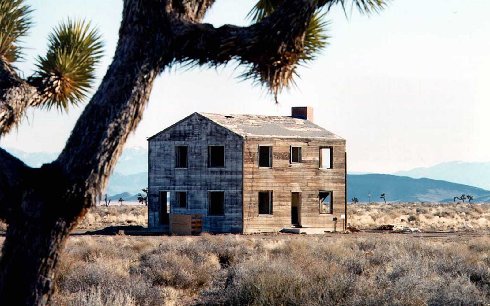 "This ""Survival Town"" house, photographed recently, was built some 7,500 feet from a 29-kiloton nuclear detonation—it remained essentially intact. Survival Town consisted of houses, office buildings, fallout shelters, power systems, communications equipment, a radio broadcasting station, and trailer homes. The test, called Apple II, was fired on May 5, 1955."