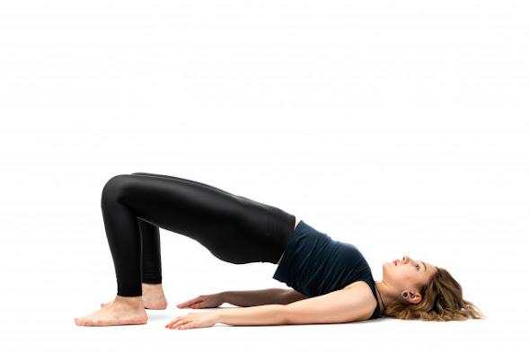 mulher loira de calça legging em posição de levantamento de quadril em casa