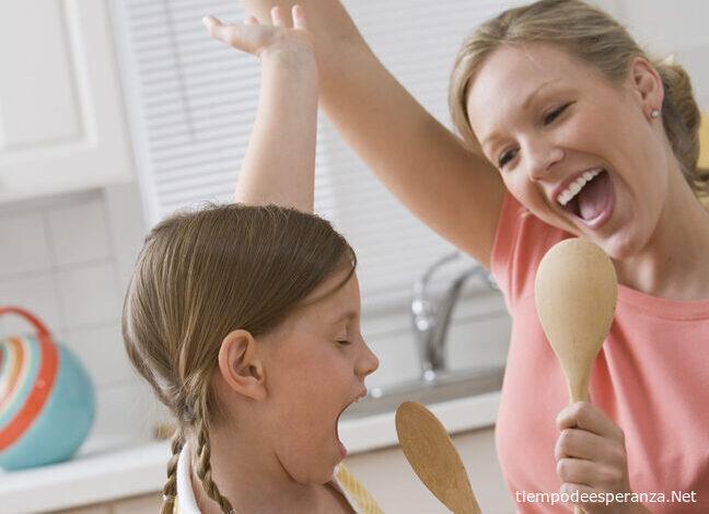 Madre y su hija cantando en la cocina