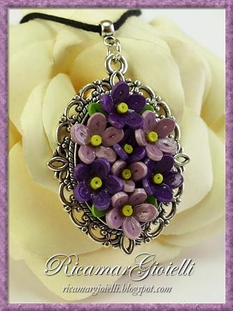 Ciondolo realizzato con piccoli fiori di carta lavorati in quilling e montati su una base di metallo