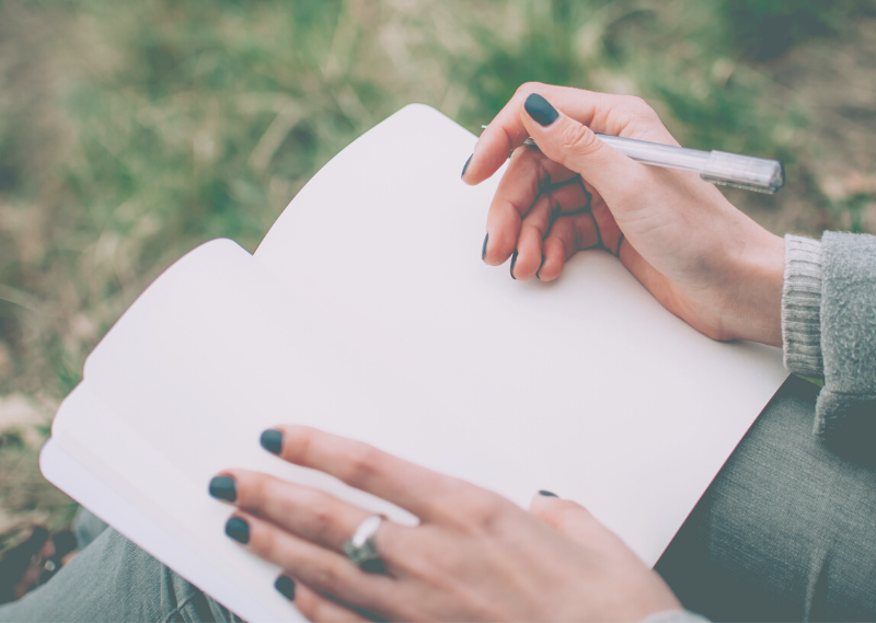 A lady writing in her journal in a post about the fantastic benefits of journaling for your wellbeing.