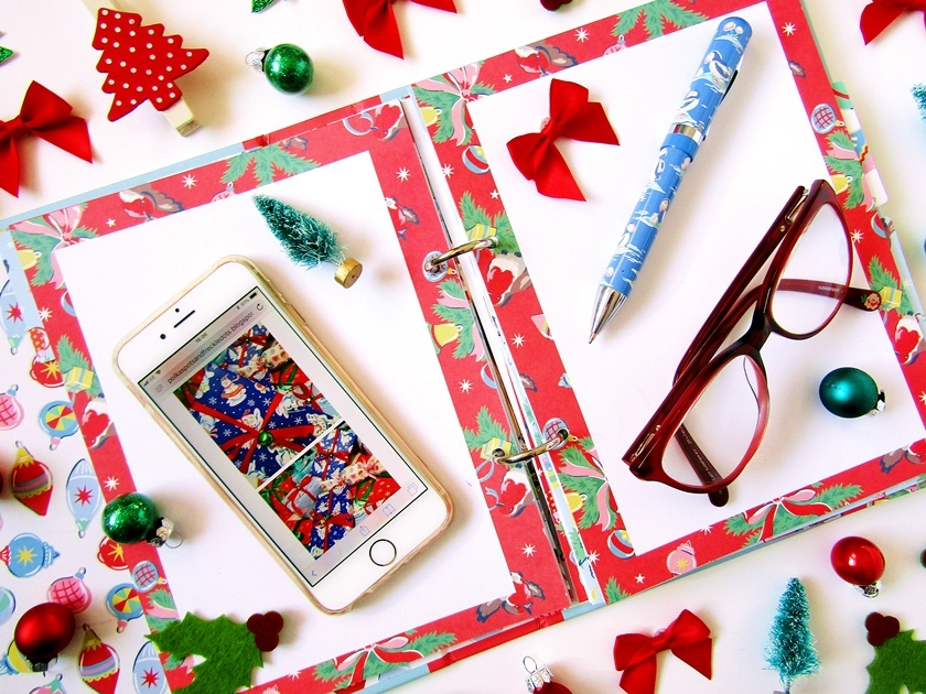 A Christmas flatlay image taken from above showing an open Christmas organiser layered with an  iPhone, pen, and a pair of red glasses, surrounded by small Christmas decorations like mini baubles, bows, and Christmas trees in red and green.