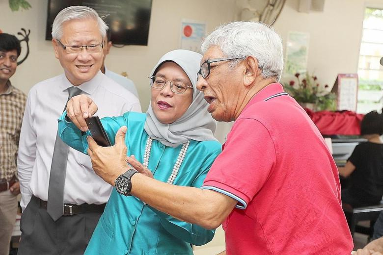 Mr Arvind Sharma takes a selfie with President Halimah Yacob as St John's Home chairman Woon Wee Yim looks on.