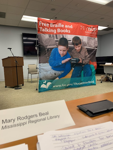 Sitting next to a lectern and microphone is a large banner that says free braille and talking books and has a picture of two boys using a TBS machine. A paper nameplate that says Mary Rodgers Beal is in the foreground.