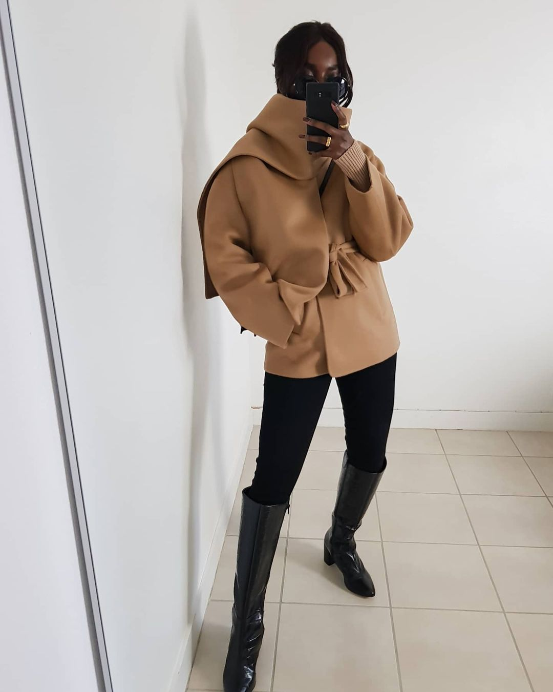 The Best Camel Pieces for Winter Outfits — @basicstouch Aïda San in a camel coat, csweater, black jeans, and knee-high boots