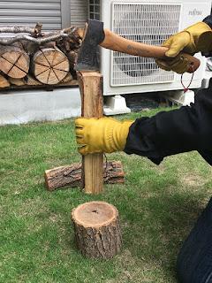 斧の刃を薪にあてて持ち上げる