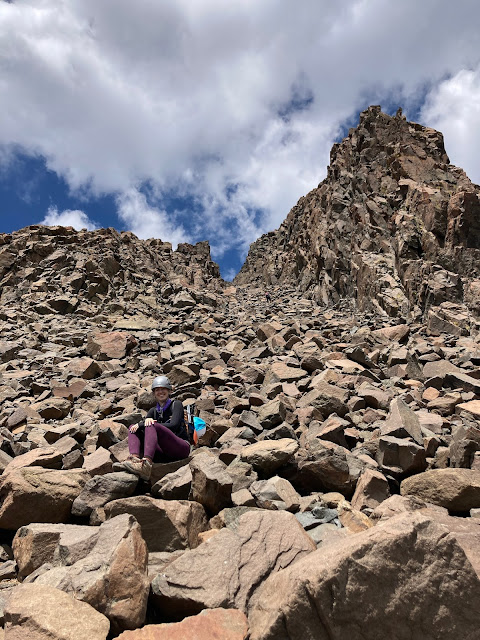 woman sitting in a rock gully leading to a mountain top