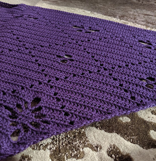 An angle photo of crochet purple shawl laid flat on carpet, the shawl has flower and butterfly motifs in a grid pattern.