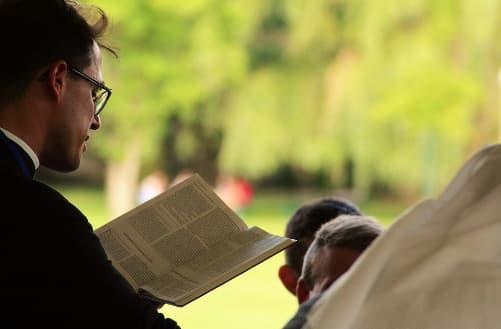 A imagem mostra a foto de perfil de um homem de terno pregando a palavra de Deus com uma bíblia aberta nas mãos para um público fiel ao fundo.