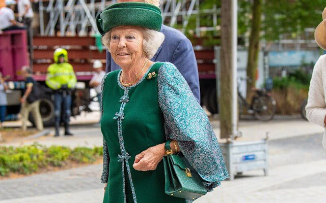 The Princess wore a green embroidered skirt suit, embroidered cape and green hat, gold brooch