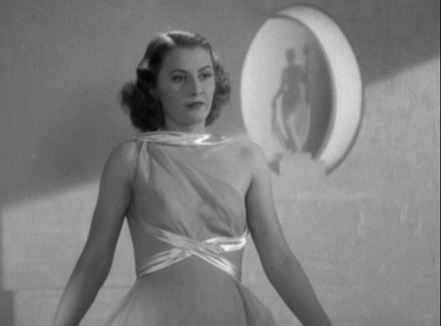 Barbara Stanwyck models an evening gown in the film.
