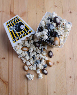 containers of cookies and cream popcorn with little candy footballs added