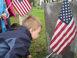 Student replacing a flag at a gravestone