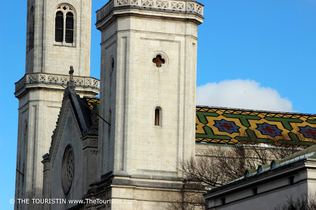 Glimpse of the tiled roof of a white neo-Romanesque style church.