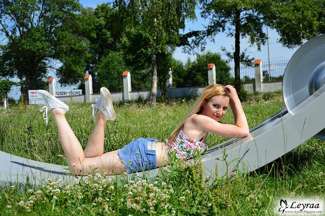 Bralet floral, szorty jeansowe z postrzępionymi nogawkami, białe trampki, wianek w pastelowe kwiaty