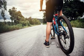 homem de bicicleta em uma estrada vazia