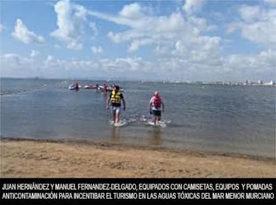Juan Hernández y manuel Fernandez, equipados con trajes anticontaminación intentan engañar a turistas y veraneantes para que se bañen en las aguas tóxicas del mar muerto español