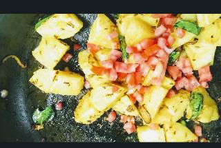 Mixing tomato into potato mixture for Jeera aloo recipe