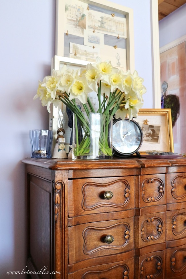 A French Prints Shadowbox hangs above a small antique chest of drawers