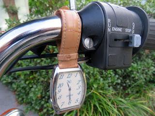 Wrist watch hanging from handlebar.