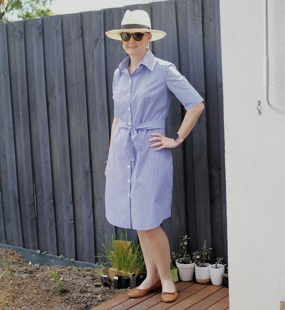 a white lady posing in a blue and white shirt dress with hat in front a paling fence
