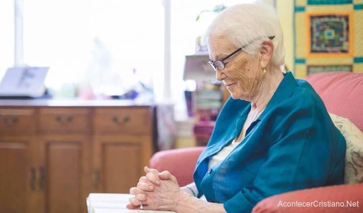 Anciana orando con Biblia