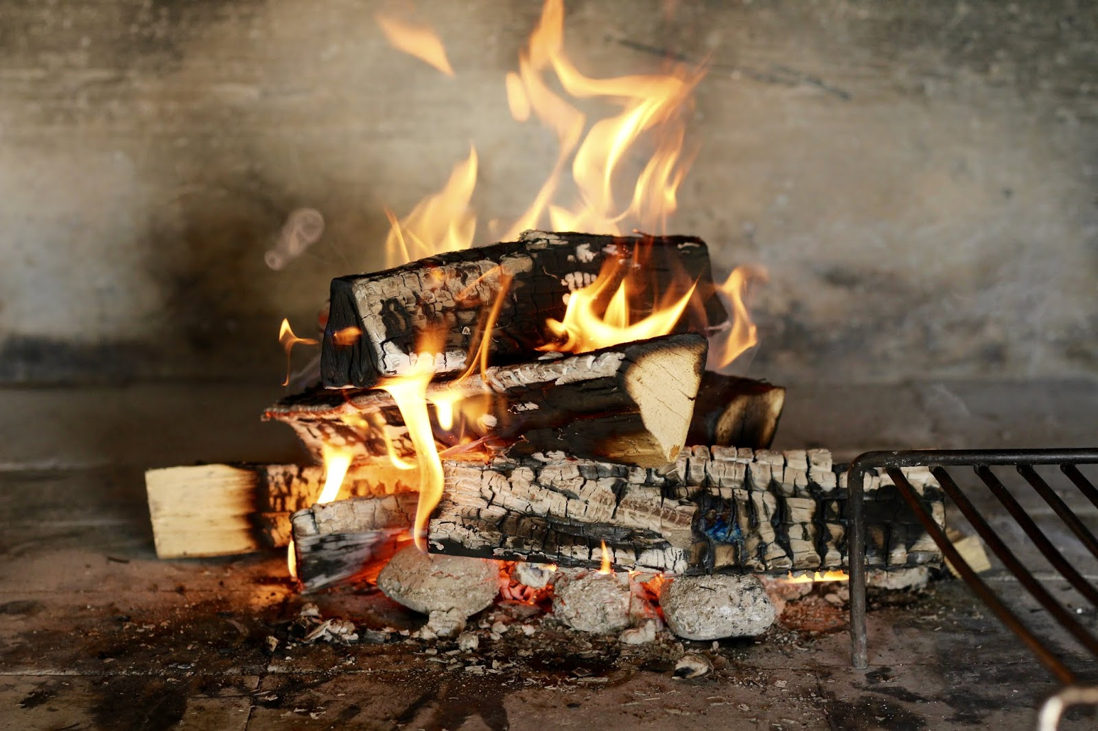 """Unser tägliches Grillfeuer im traditionellen """"Komin"""" in der Außenküche"""