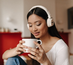 A tanned woman with dark hair wearing a white top she is holding a white mug and is wearing white headphones