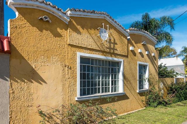 Uma casa amarela com platibanda