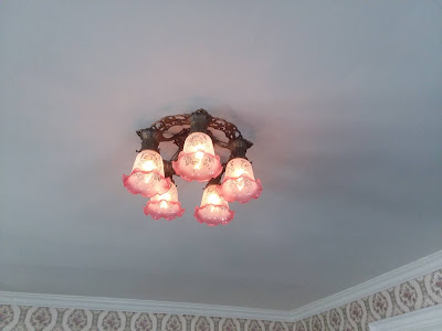 Close-up of one of the antique chandeliers with five pink etched domes