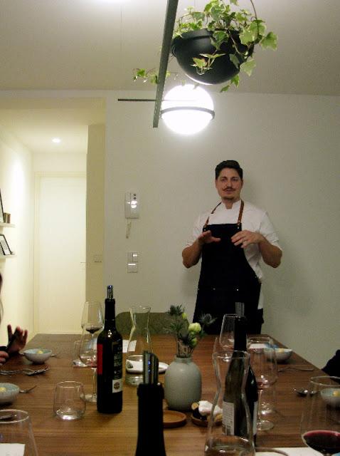 chef explicando suas criações em frente de mesa de jantar