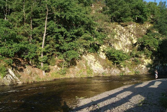 Bewachsene Sandsteinfelsen, vor denen ein Fluss fließt