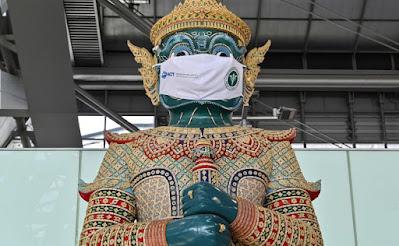 Patung tradisional Thailand mengenakan masker sebagai kampanye bagi para pelancong untuk mencegah penyebaran virus corona Covid-19 di terminal keberangkatan Bandara Suvarnabhumi di Bangkok pada 30 Juni 2021. AFP