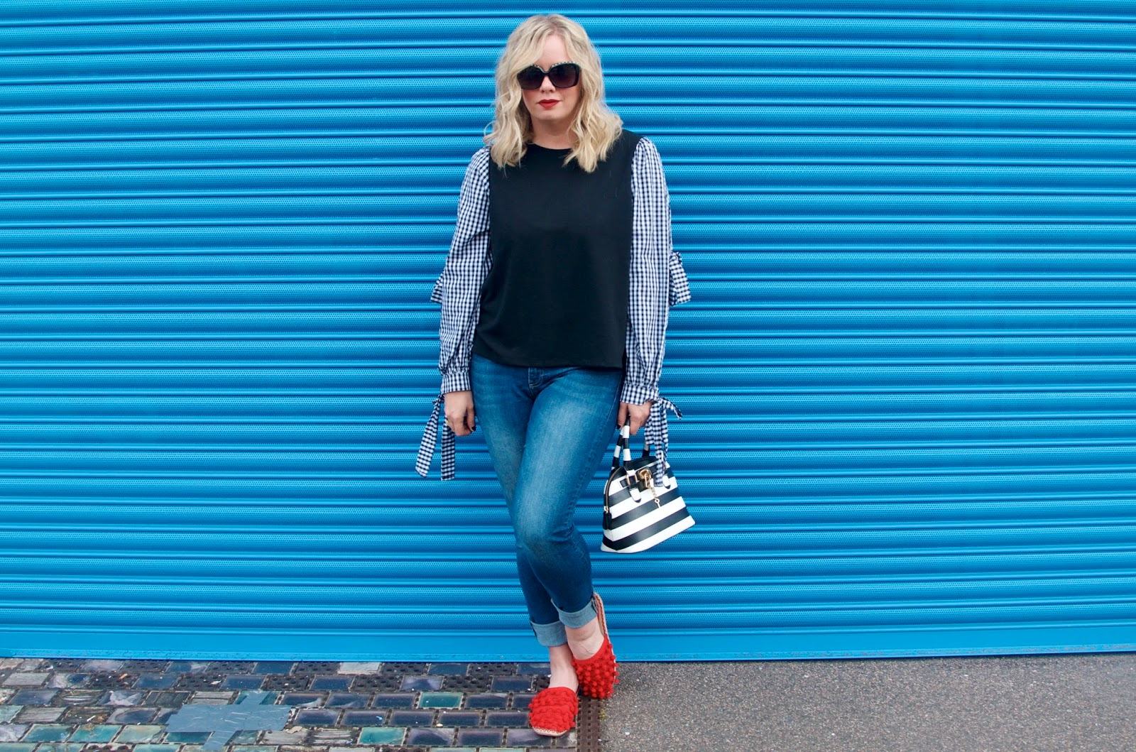 blue wall, gingham sleeves, red shoes, jeans and striped bag