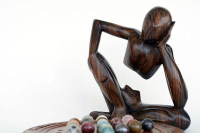 تمثال خشب يجلس بصبر وإنتظار و أمامه كرات خشبية