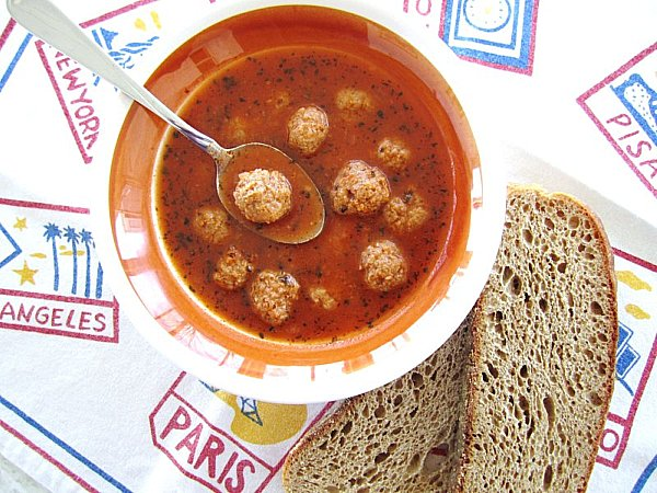 A bowl of Armenian meatball soup with sliced wheat toast next to the bowl