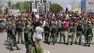 aksi dengan pengawalan prajurut TNI di Bundaran Timika Indah, Mimika, Papua