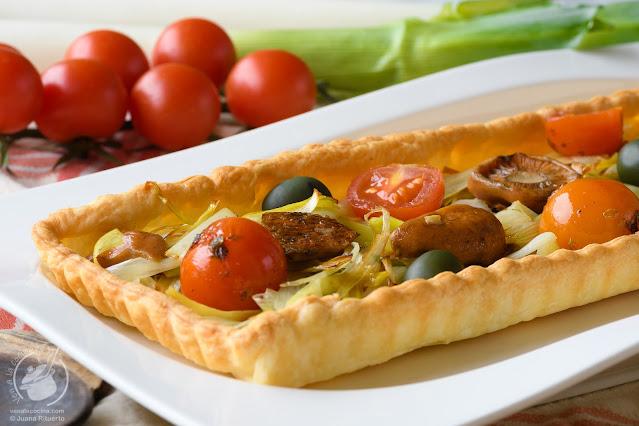 Hojaldre de puerros con níscalos, tomate y aceitunas