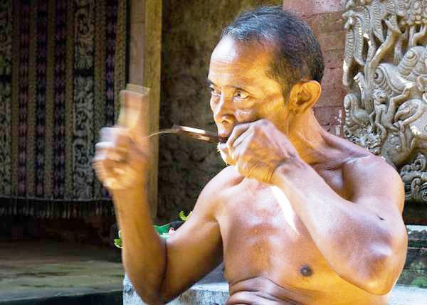 Orang Bali yang sedang memainkan alat musik Genggong