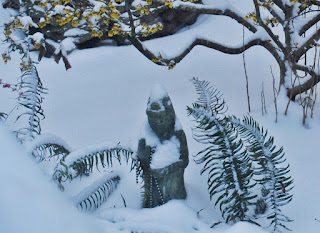 Kwan Yin and trees and ferns covered with snow