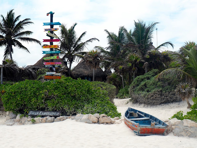 Old fishing boat and colourful direction sign on Tulum beach, Mexico