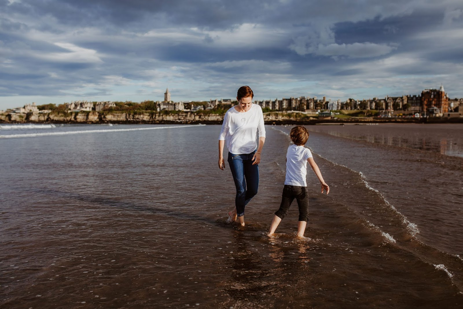 mother and child playing in shallow water on West Sands beach St Andrews