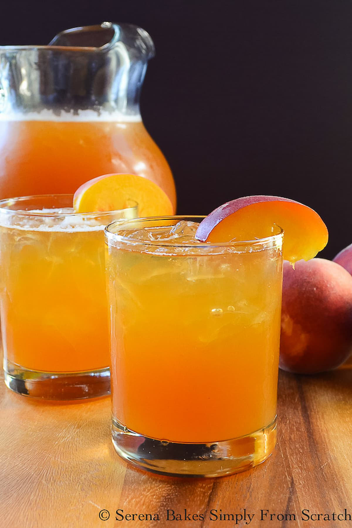 Two glasses of Peach Whiskey Iced Tea with a pitcher in the background on a wooden cutting board.