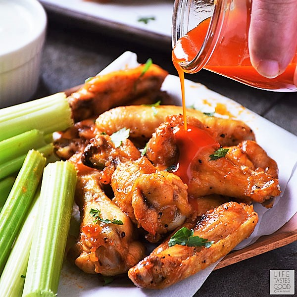 Pouring extra Buffalo wing sauce on Low Carb Buffalo Wings appetizer