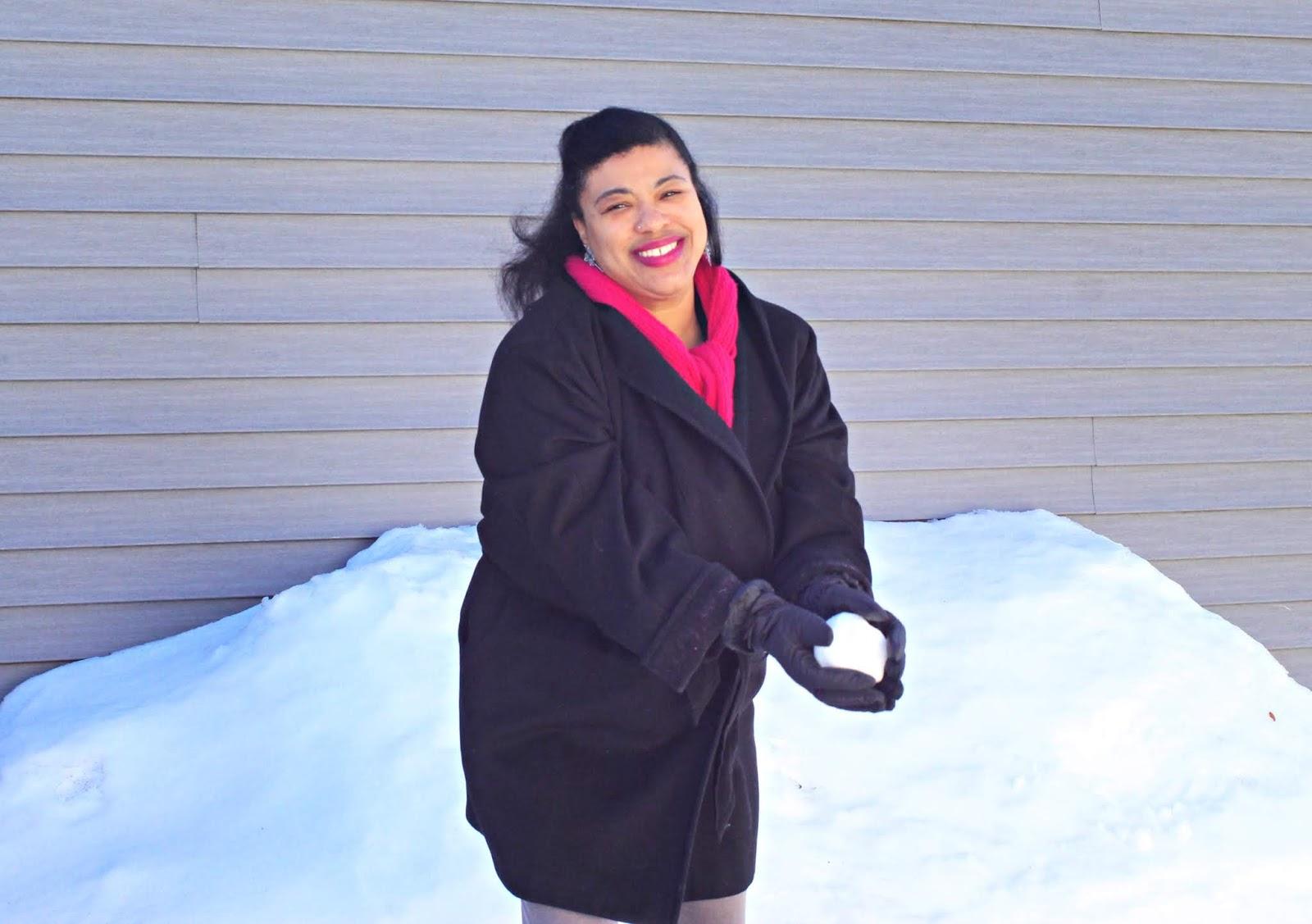 a black woman making a snowball